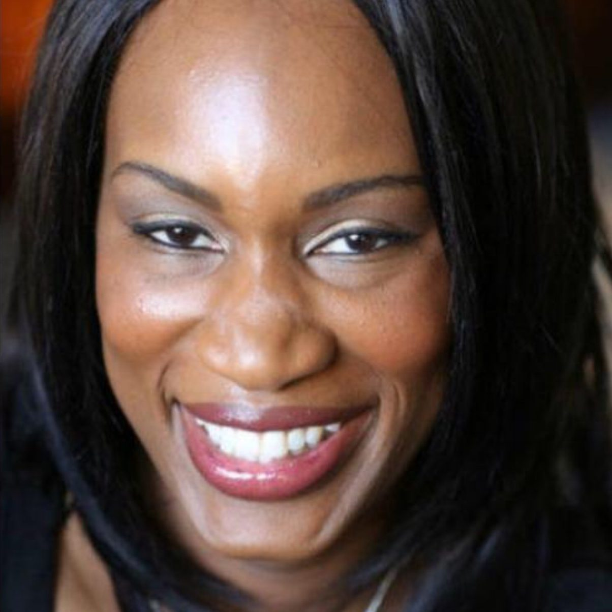 A close up picture of a black woman smiling with straight black hair